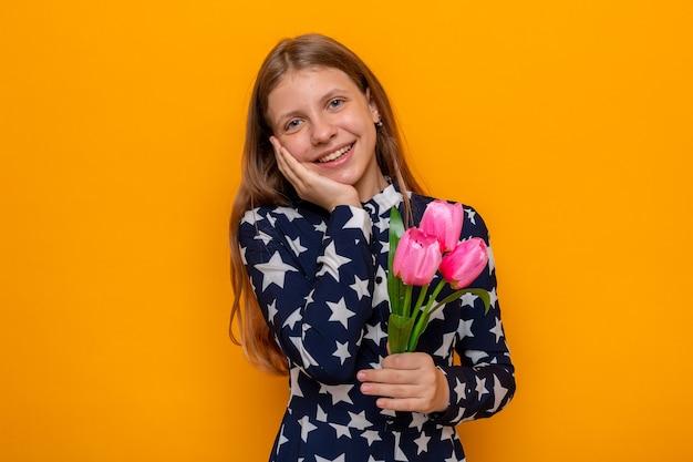 Uśmiechnięta kładąca dłoń na policzku piękna mała dziewczynka w szczęśliwy dzień kobiet trzymająca kwiaty izolowane na pomarańczowej ścianie