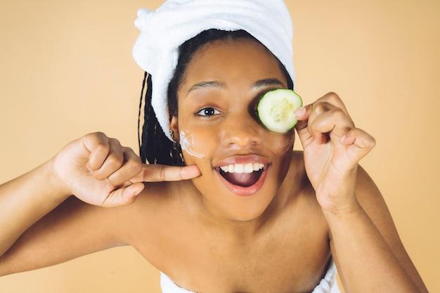 Uśmiechnięta kobieta afro otrzymuje zabieg dermaplaningu