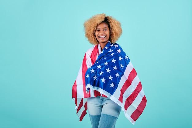 Uśmiechnięta kobieta afro owinięta amerykańską flagą, stojąc na odosobnionym tle. koncepcja obchodów dnia niepodległości.