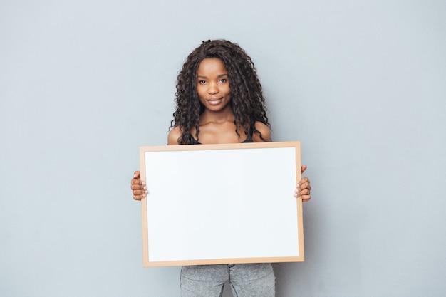 Uśmiechnięta kobieta afro pokazująca pustą deskę nad szarą ścianą