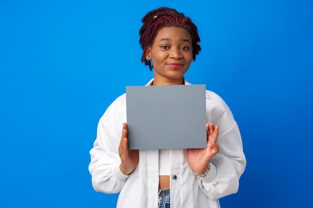Uśmiechnięta kobieta afro pokazująca pusty szary papier na niebieskim tle