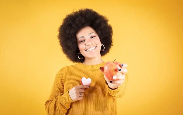 Uśmiechnięta kobieta afro trzymająca w jednej ręce jabłko, az drugiej serce na żółtym tle
