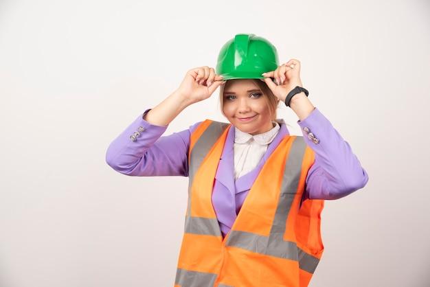 Uśmiechnięta kobieta architekt w kasku na białym.