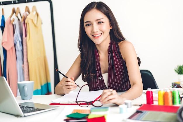 Uśmiechnięta kobieta azji projektant mody pracuje
