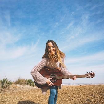Uśmiechnięta kobieta bawić się gitarę w naturze
