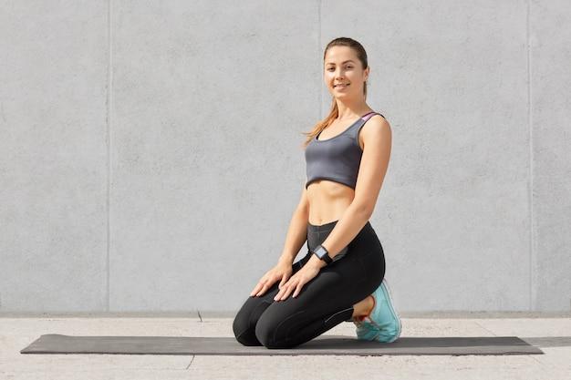 Uśmiechnięta kobieta będąca w dobrym modzie po zrobieniu brzuszków na macie fitness, stoi na kolanach, ubrana w odzież sportową, ma zdrowe ciało