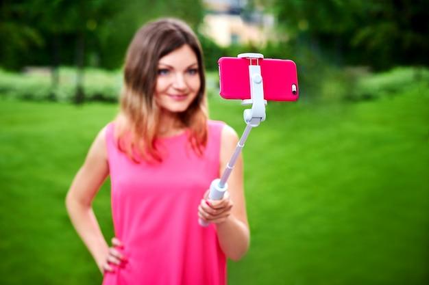 Uśmiechnięta kobieta bierze selfie na telefonie komórkowym z kijem outdoors