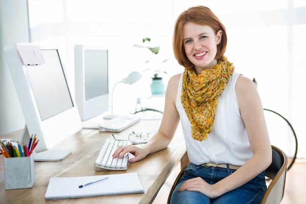 Uśmiechnięta kobieta biznesu hipster siedzi przy biurku, ubrany w szalik