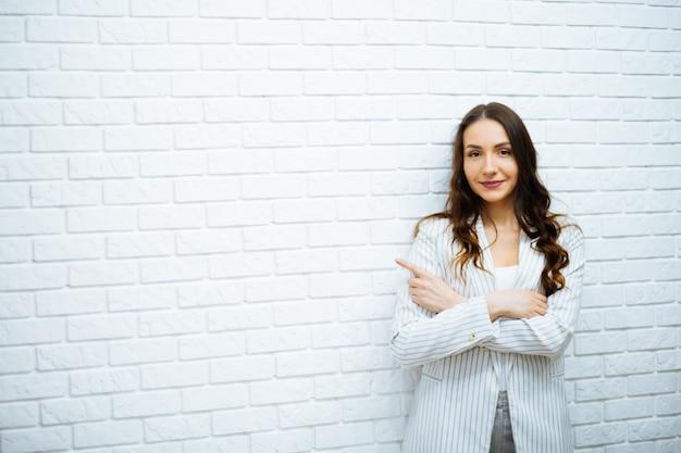 Uśmiechnięta kobieta biznesu pokazując zęby w pracy z długimi ciemnymi włosami w białej kurtce z rękami na brzuchu i wskazując palcem na prawą rękę rysuje na białej ścianie