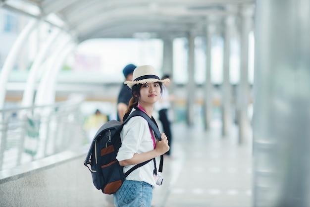 Uśmiechnięta kobieta chodzi outdoors, młoda dama podziwia widok miasta z przejściem i budynkami w tle.
