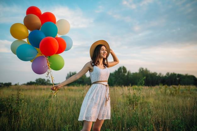 Uśmiechnięta kobieta chodzi w zielonym polu z kolorowymi balonami. ładna dziewczyna na letniej łące w słoneczny dzień