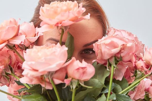 Uśmiechnięta kobieta chowa twarz za bukietem pachnących różowych róż. walentynki. dzień kobiet. zbliżenie,