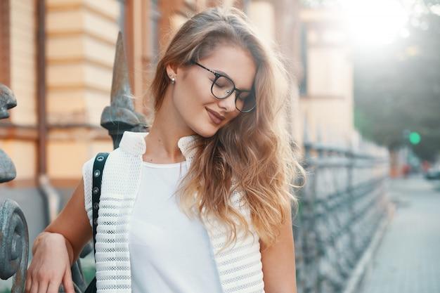 Uśmiechnięta kobieta cieszy się światło słoneczne z zamkniętymi oczami podczas gdy odpoczywający