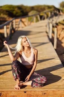 Uśmiechnięta kobieta cieszy się zmierzch na pięknej plaży