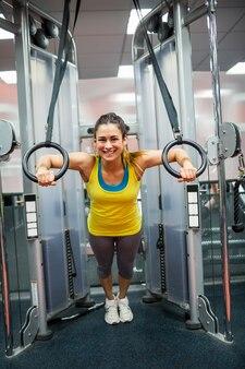 Uśmiechnięta kobieta ćwiczy ona ręki