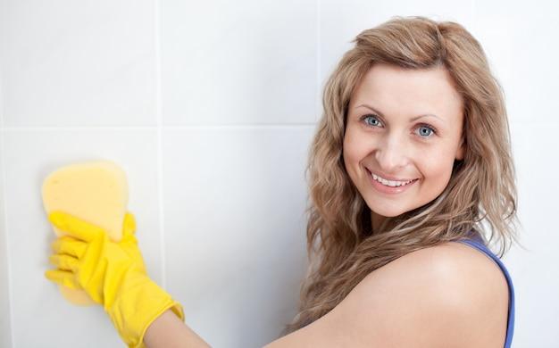 Uśmiechnięta kobieta czyści łazienkę