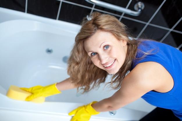 Uśmiechnięta kobieta czyści skąpanie