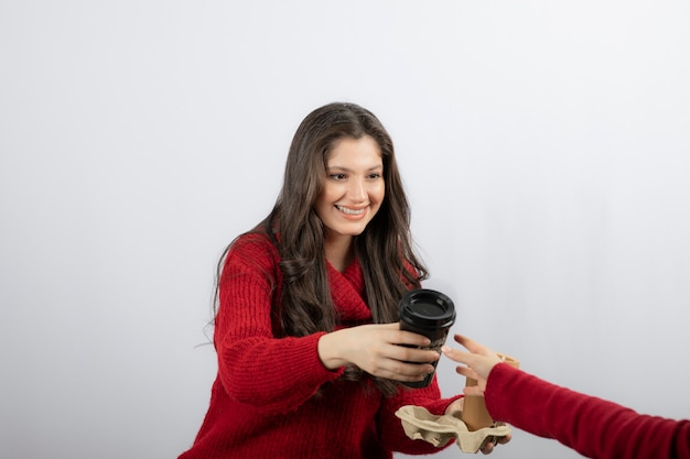 Uśmiechnięta kobieta daje filiżankę napoju na białej ścianie.