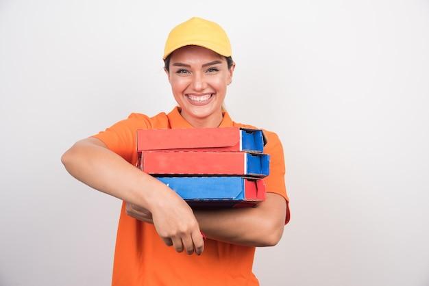 Uśmiechnięta kobieta dostawy trzymając pudełka po pizzy na białej przestrzeni