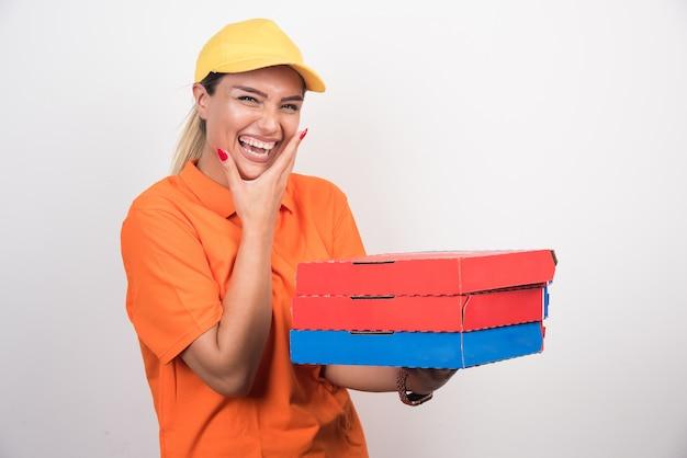 Uśmiechnięta kobieta dostawy trzymając pudełka po pizzy, trzymając twarz na białej przestrzeni
