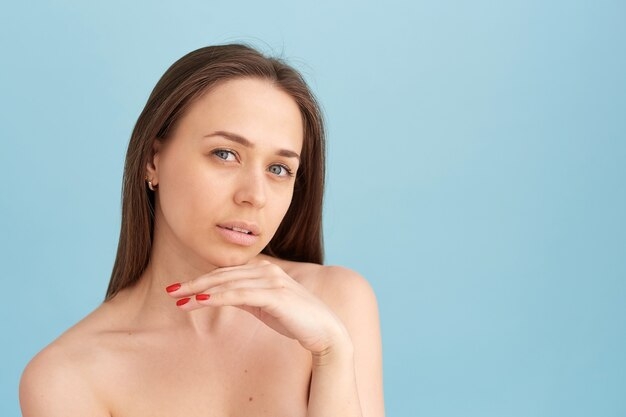 Uśmiechnięta kobieta dotyka jej twarzy na niebieskim tle. koncepcja naturalnego piękna, szczęśliwa kobieta.