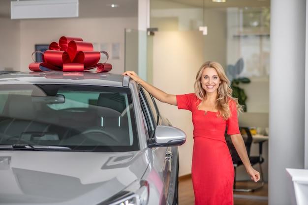 Uśmiechnięta kobieta dotykająca samochodu z kokardą