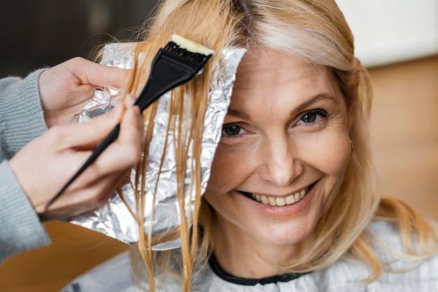 Uśmiechnięta kobieta farbuje włosy przez fryzjera w domu