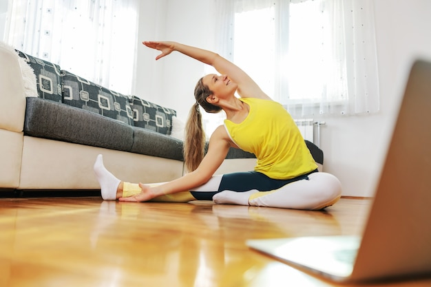 Uśmiechnięta kobieta fit jogi siedzi na podłodze w domu w pozycji jogi od głowy do kolan i śledzi zajęcia online.