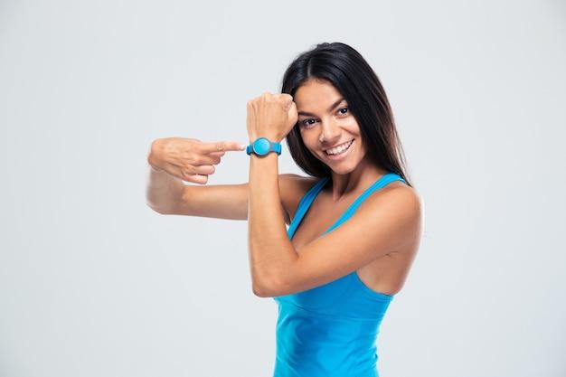 Uśmiechnięta kobieta fitness, wskazując na urządzenie do śledzenia sprawności