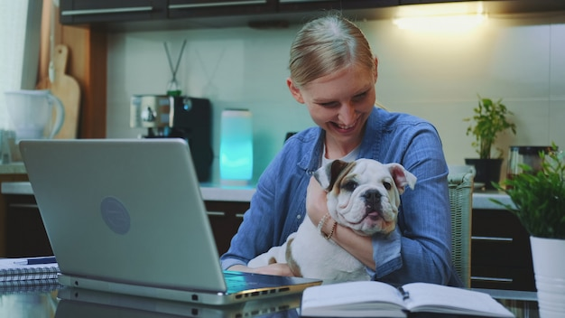 Uśmiechnięta kobieta gładzi buldoga i ściska podczas gdy siedzący przy komputerem