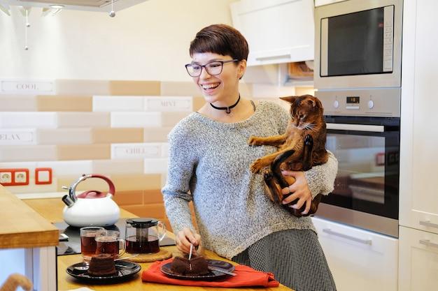 Uśmiechnięta kobieta gra z imbirowym kotem i jedzenie ciasta w kuchni