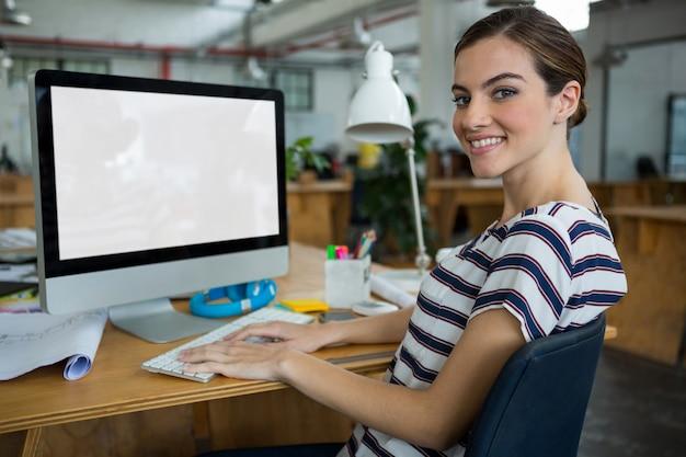 Uśmiechnięta kobieta grafik pracujący na komputerze