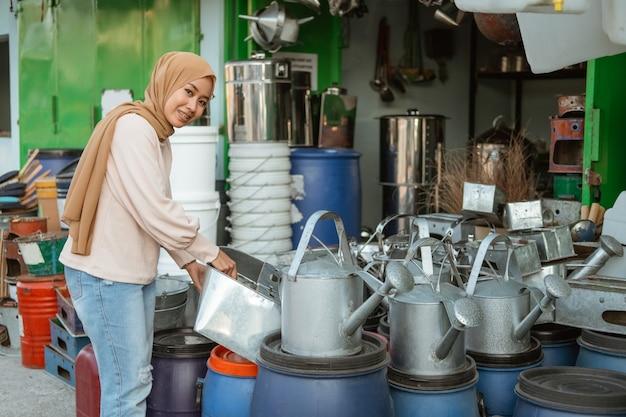Uśmiechnięta kobieta hidżab stoi trzymając konewkę w sklepie agd