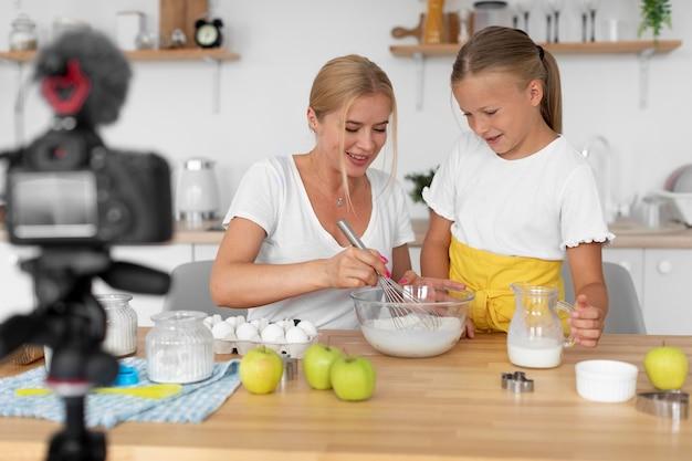 Uśmiechnięta kobieta i dziewczyna gotują