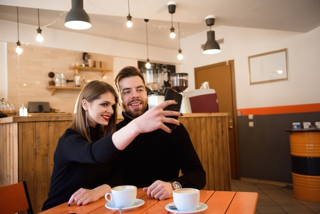 Uśmiechnięta kobieta i przystojny mężczyzna picia kawy, za pomocą telefonu komórkowego spędzając czas w kawiarni.