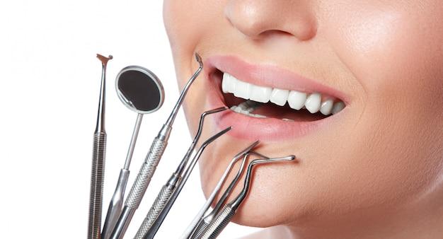 Uśmiechnięta kobieta i stomatologiczni narzędzia