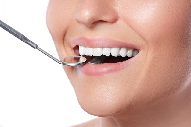 Uśmiechnięta kobieta i stomatologiczny lustro