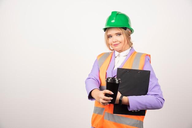 Uśmiechnięta kobieta inżynier przemysłowy w mundurze ze schowka i czarny kubek na białym tle.