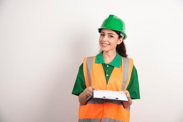 Uśmiechnięta kobieta inżynier ze schowkiem na białym tle. zdjęcie wysokiej jakości