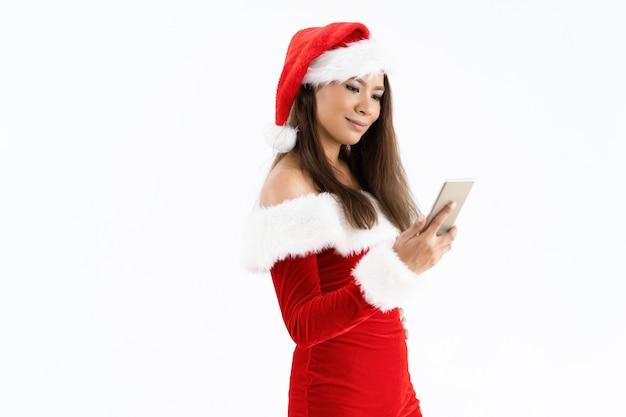Uśmiechnięta kobieta jest ubranym bożenarodzeniowego kostium i używa smartphone