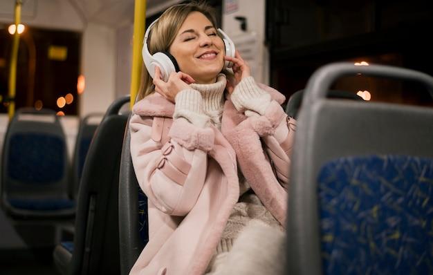 Uśmiechnięta kobieta jest ubranym hełmofony siedzi w autobusie