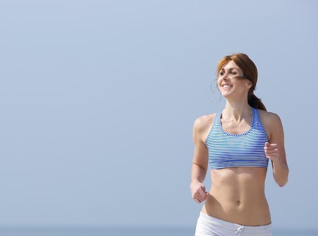 Uśmiechnięta kobieta jogging outdoors