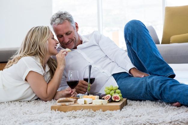 Uśmiechnięta kobieta karmi jedzenie mężczyzna podczas gdy kłamający na dywaniku