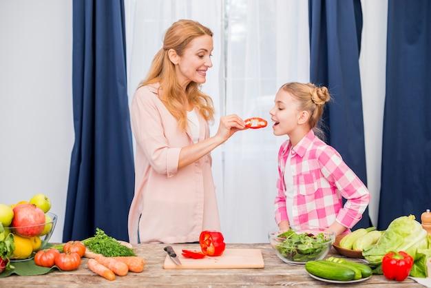 Uśmiechnięta kobieta karmi plasterek dzwonkowy pieprz jej córka