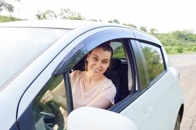 Uśmiechnięta kobieta kierowca siedzi w swoim samochodzie, okno jest otwarte, kobieta patrzy na kamerę.