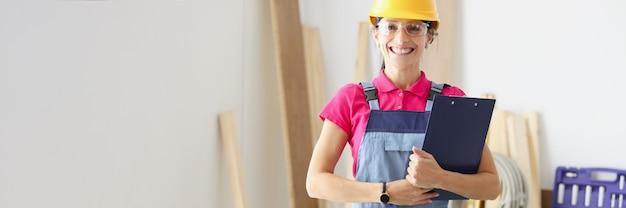 Uśmiechnięta kobieta konstruktora trzyma w dłoniach schowek z dokumentami