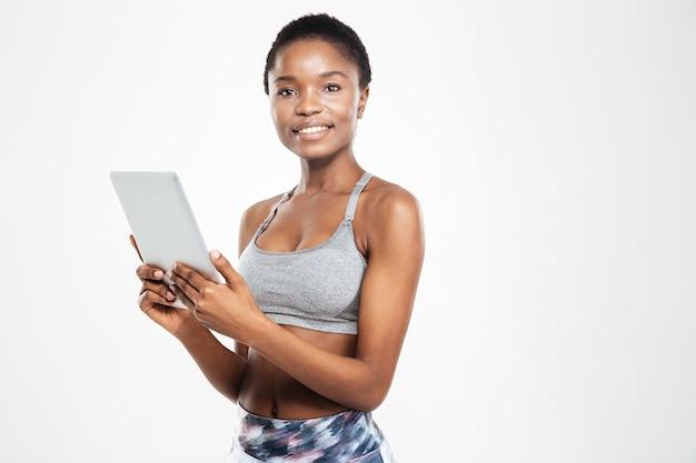 Uśmiechnięta kobieta korzystająca z komputera typu tablet i patrząca na przód na białej ścianie