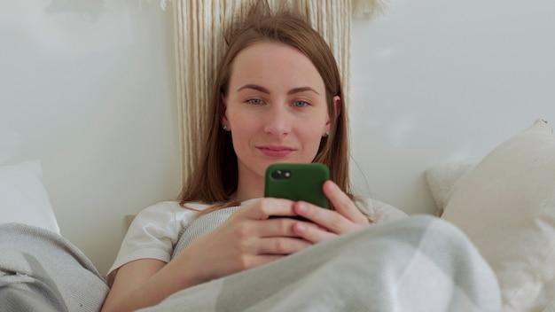 Uśmiechnięta kobieta korzystająca z telefonu komórkowego leżała na łóżku