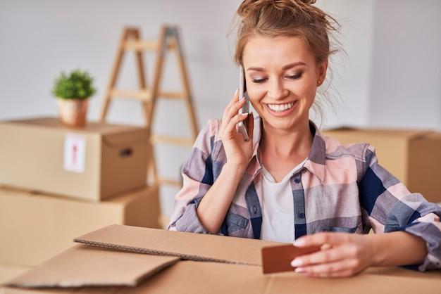 Uśmiechnięta kobieta korzystająca z telefonu podczas przeprowadzki