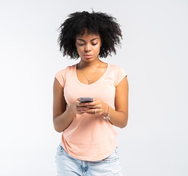 Uśmiechnięta kobieta kręcone z smartphone w rękach, patrząc w kamerę na białym.